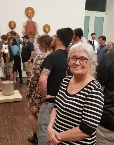 Gail Ray standing in a group of onlookers at the Figge Museum with her work hanging on the wall in the background