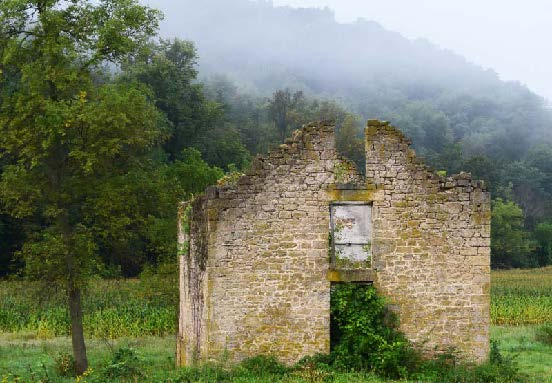 Geoffrey Mikol's piece, Embraced by Fog, a photograph of an old stone structure in front of a foggy hillside