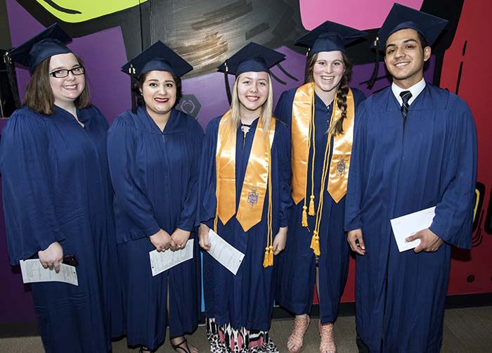 Students in blue cap and gowns standing for photo