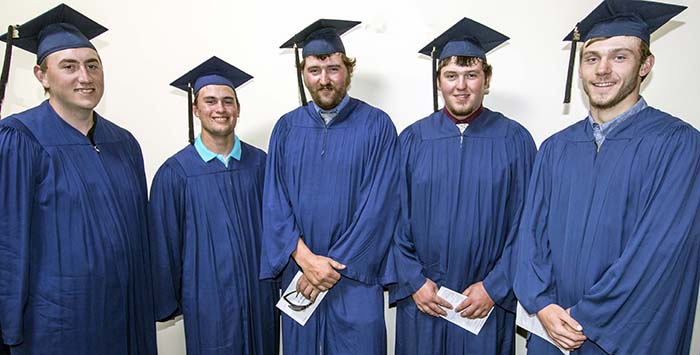5 male students standing for photo in blue caps and gowns