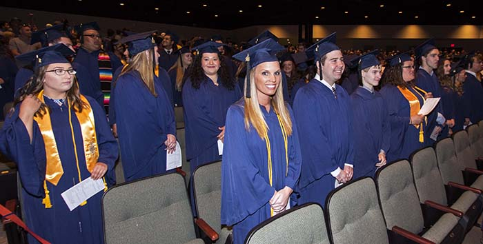 Students in blue caps and gowns standing in rows during commencement ceremony