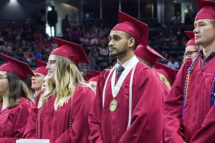 Graduates standing in rows during commencement ceremony
