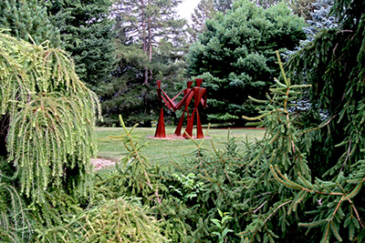 Red ring of life sculpture framed by evergreen trees