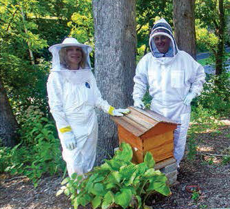 Don and Lyn standing with their beehive in protective gear