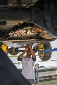 Claudy Pierre-Charles working underneath a car